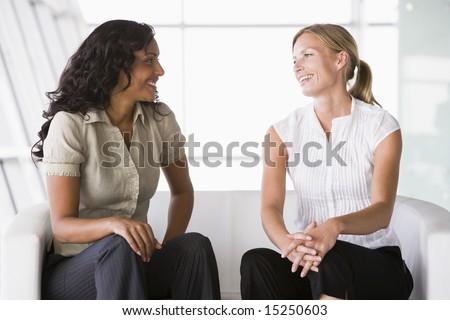 Businesswomen talking in office lobby - stock photo