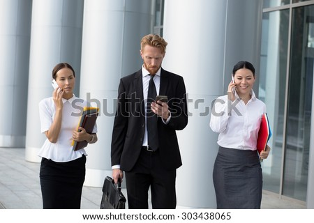 Businesswomen using cell phones while walking on path outside office. Man in black busines suit with brief case going to call to his secretary. - stock photo