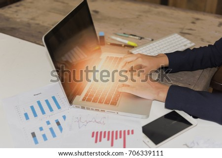 Businesswomen using laptop at desk in office.