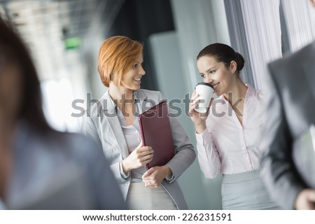 Businesswomen walking in office corridor - stock photo