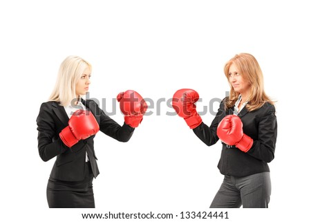 Businesswomen with boxing gloves having a fight isolated against white background - stock photo