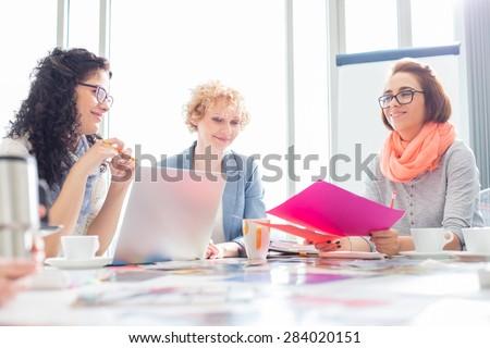 Businesswomen working at desk in creative office - stock photo