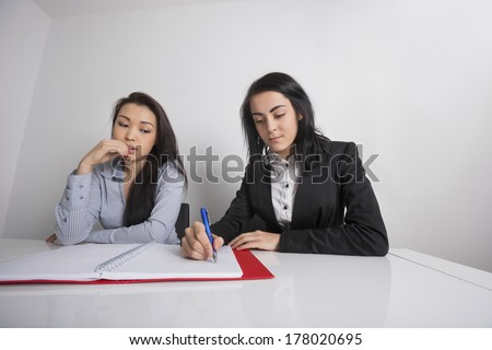 Businesswomen working at desk in office - stock photo