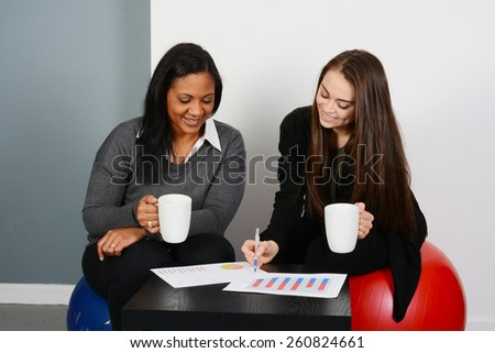 Businesswomen working on a project while in an office - stock photo