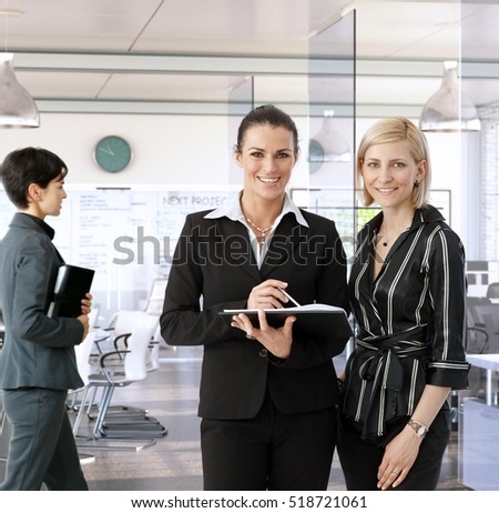 Businesswomen working together at office, smiling.