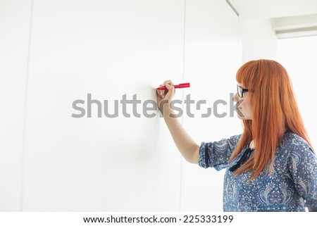 Businesswomen writing on whiteboard in creative office - stock photo