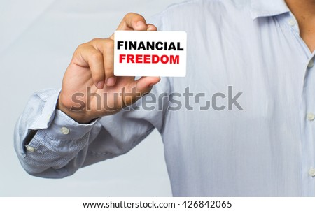 Businnss hands holding white card sign with Financial freedom text message isolated on grey wall office background. Retro instagram style image - stock photo