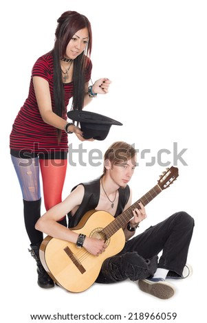 Buskers play and sing on guitar. Asian woman and Caucasian man.  - stock photo