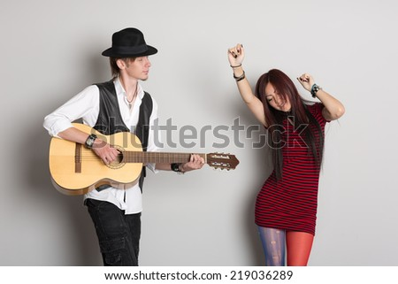 Buskers play the guitar and dance. Asian woman and Caucasian man.