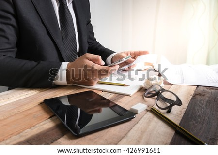 Bussiness concept, Bussiness man working with bill and smartphone on wooden table