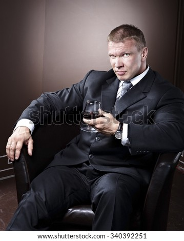 Bussiness man boss sitting and smiling with a glass of wine - stock photo