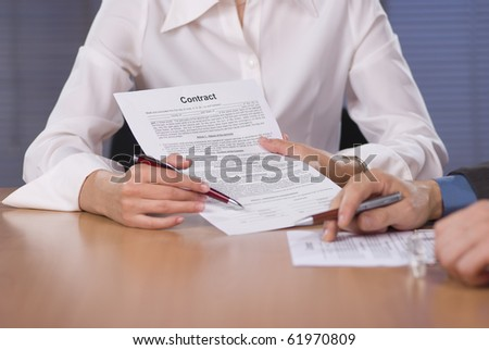 Bussinesswoman (or notary public) holding pen pointing to bussinessman at signature place on a contract document - stock photo