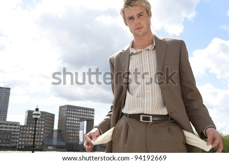 Bust businessman pulling out his empty pockets. - stock photo