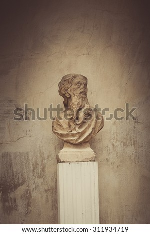 bust of a bearded man near the wall, under the old photo processing, sepia