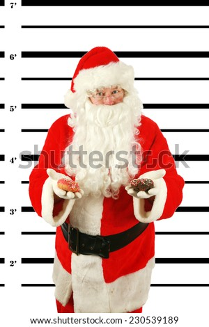 BUSTED. Santa Claus is arrested and his MUG SHOT taken at the Police Station. Santa was a Bad Bad boy.  He even tried to Bribe his Freedom from the Police with Donuts knowing they are hard to resist. - stock photo