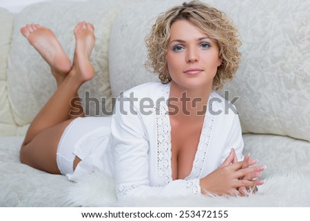 Busty beautiful girl lying on the sofa - stock photo