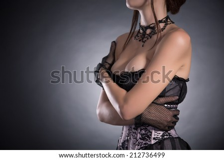 Busty woman in elegant pink and black corset with floral pattern, studio shot  - stock photo