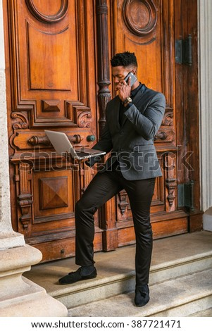 Busy African American Businessman working in New York, wearing fashionable jacket, stepping on stairs by vintage library doorway, looking down, working on laptop computer, talking on phone.
