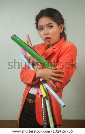Busy Asian business woman with a lot of colorful  papers  on  background.