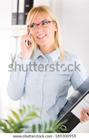 Busy Beautiful Businesswoman with glasses use mobile phone in the office and holding documents.