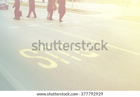 Busy big city street people on zebra crossing and bus lane painted on the street - stock photo