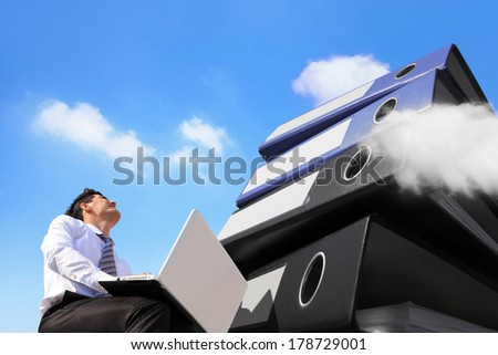 Busy business man working with computer and lots piles of folders with sky and cloud - stock photo