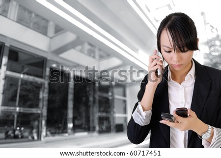 Busy business woman calling and reading by phone outside buildings. - stock photo
