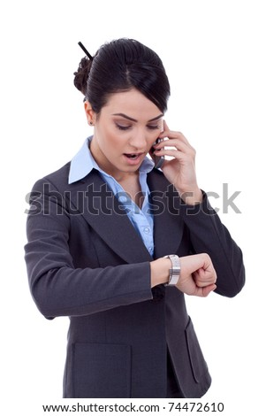 Busy business woman checking the time while calling. - stock photo