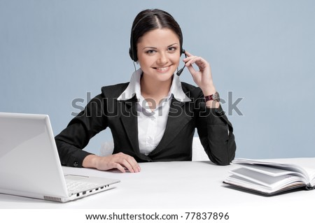 Busy business woman in office place communicate by wireless headset over white table, laptop and diary.