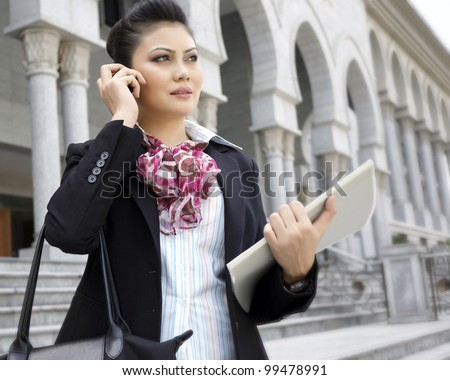 Busy business woman talking on phone while holding files - stock photo