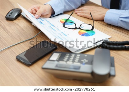busy businessman analyzing a lot of  graphs and business data at  the desk - stock photo