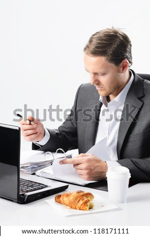 Busy businessman has to sign documents and look over contracts, no time to finish breakfast croissant - stock photo