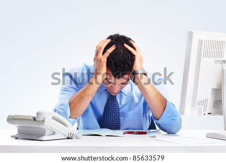 Busy businessman having headache at the office. - stock photo