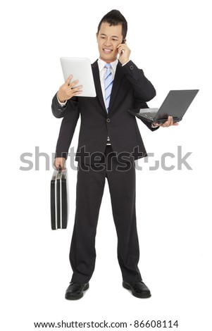busy businessman holding mobile phone and laptop and tablet pc and briefcase - stock photo