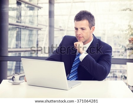 Busy businessman in suit working with laptop at office desk, concentrating, thinking. - stock photo