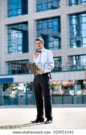 busy businessman with documents front of office building