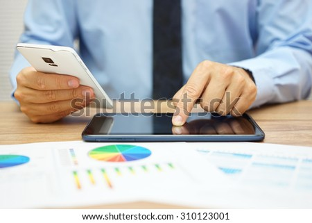 busy businessman  with financial documents working in office with tablet computer and smart phone at the same time - stock photo