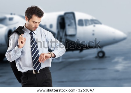 Busy businessman with jacket on his shoulder looking at his watch on the airport - check my portfolio for similar photos - stock photo