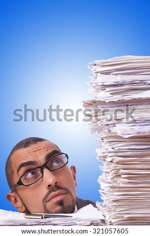 Busy businessman with lots of papers - stock photo