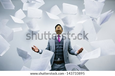 Busy businessman with pile of papers flying on air - stock photo