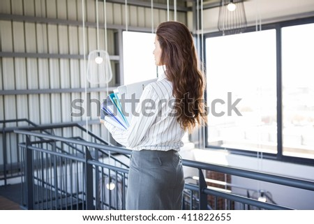 Busy businesswoman carrying stack of folders with files documents in office - stock photo