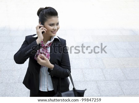 Busy Businesswoman smile while using phone - stock photo