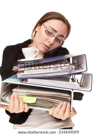 Busy businesswoman with a lot of folders and cup of coffee calling by phone