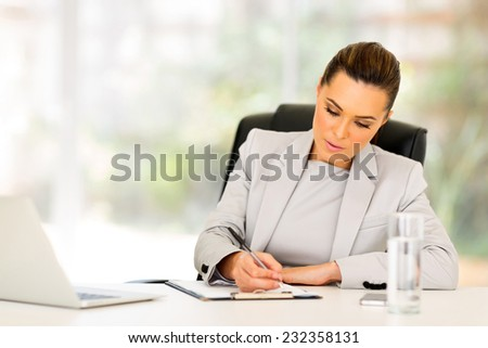 busy businesswoman working in modern office - stock photo