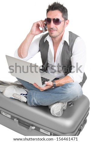 Busy Caucasian man sitting on suitcase while talking on mobile phone - stock photo