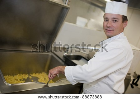 Busy chef preparing meal in restaurant kitchen - stock photo