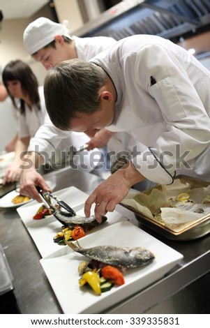 Busy chefs at work in the restaurant kitchen  - stock photo