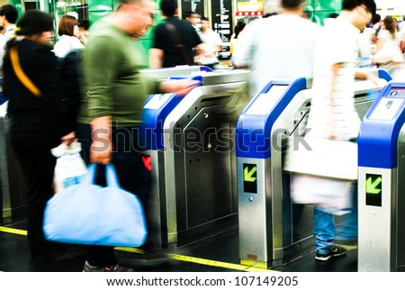 Busy city people walking in subway station in motion blur - stock photo