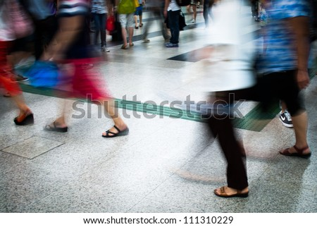Busy city people walking in subway station in motion blur