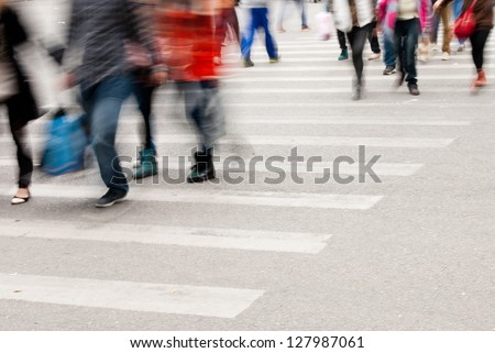 Busy city street people on zebra crossing - stock photo